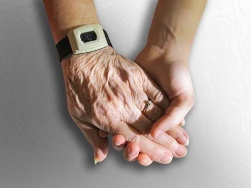 Ilustrativna slika mlade ruke kako drži staru ruku