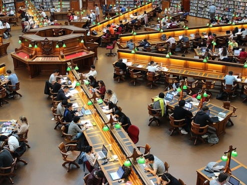 Ilustrativna slika stolova i čitača u knjižnici
